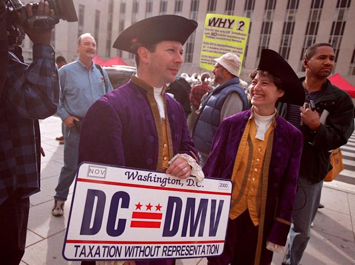 """Mark Phillips and Karen Beriss show off an enlarged version of the new """"Taxation Without Representation"""" license plate in Washington, D.C., on Nov. 4, 2000."""