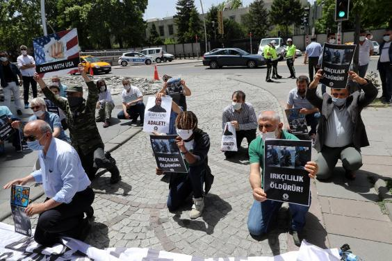 Protesters kneel and hold placards in Ankara, during a demonstration against racism and police brutality (AFP/Getty)