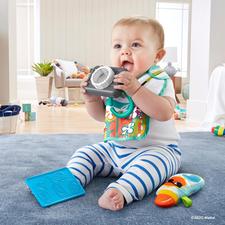 """The Fisher-Price Tiny TouristGift Set ($14.99, available now) includes a toy camera with a clicking lens and rattlingbeads, sunscreen bottle and a chewable teething """"passport,"""" and amirror."""