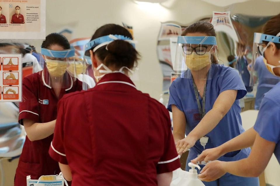 <p>Medical staff don PPE at Craigavon Area Hospital in Co Armagh, Northern Ireland</p> (PA)