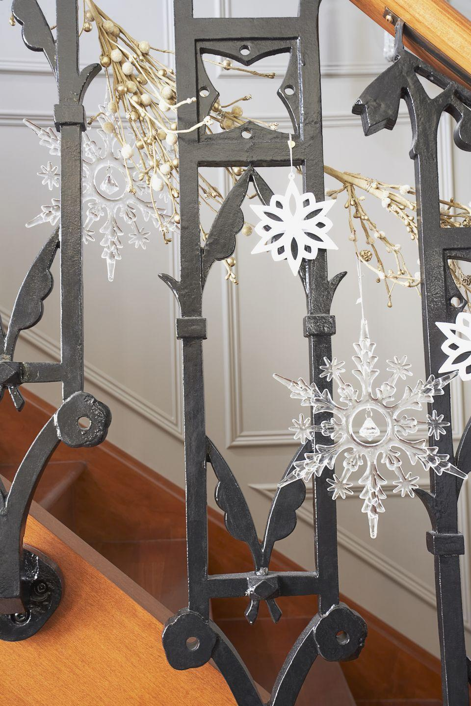 """<p>If you have dark-colored or iron spindles, a smattering of snowflakes dangling at different heights provides the perfect bannister contrast. </p><p><a class=""""link rapid-noclick-resp"""" href=""""https://www.amazon.com/Whaline-Decorations-Snowflake-Ornaments-Accessories/dp/B07Z67SFCN?tag=syn-yahoo-20&ascsubtag=%5Bartid%7C10072.g.34479907%5Bsrc%7Cyahoo-us"""" rel=""""nofollow noopener"""" target=""""_blank"""" data-ylk=""""slk:SHOP SNOWFLAKE DECORATIONS"""">SHOP SNOWFLAKE DECORATIONS</a></p>"""