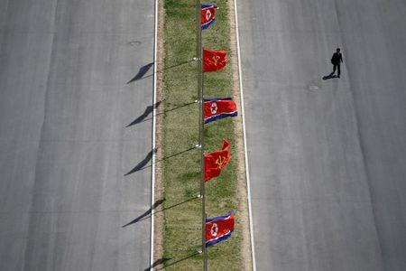 A man walks the the street decorated with flags as North Korea prepares to mark Saturday's 105th anniversary of the birth of Kim Il-sung, North Korea's founding father and grandfather of the current ruler, in central Pyongyang