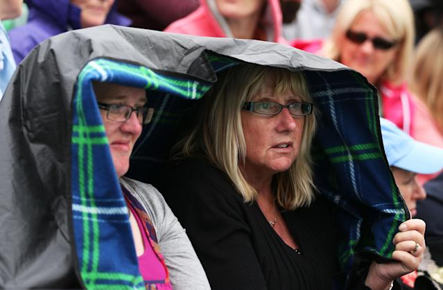 LONDON, ENGLAND - JUNE 27: Spectators shelter from the rain during day four of the Wimbledon Lawn Tennis Championships at the All England Lawn Tennis and Croquet Club on June 27, 2013 in London, England. (Photo by Clive Brunskill/Getty Images)