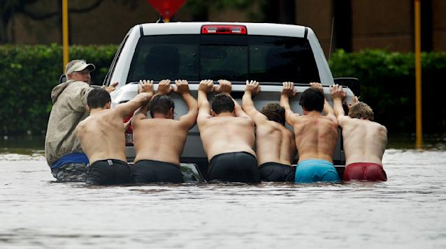 <p>People push a stalled pickup to through a flooded street in Houston, after Tropical Storm Harvey dumped heavy rains Sunday, Aug. 27, 2017. (Photo: Charlie Riedel/AP) </p>