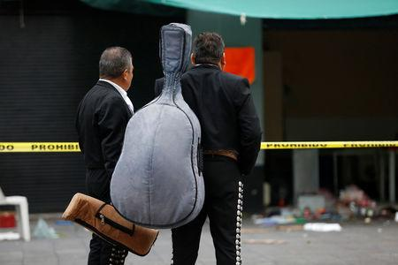 Mariachi musicians observe a crime scene hours after unknown assailants attacked people with rifles and pistols at an intersection on the edge of the tourist Plaza Garibaldi in Mexico City, Mexico September 15, 2018. REUTERS/Gustavo Graf