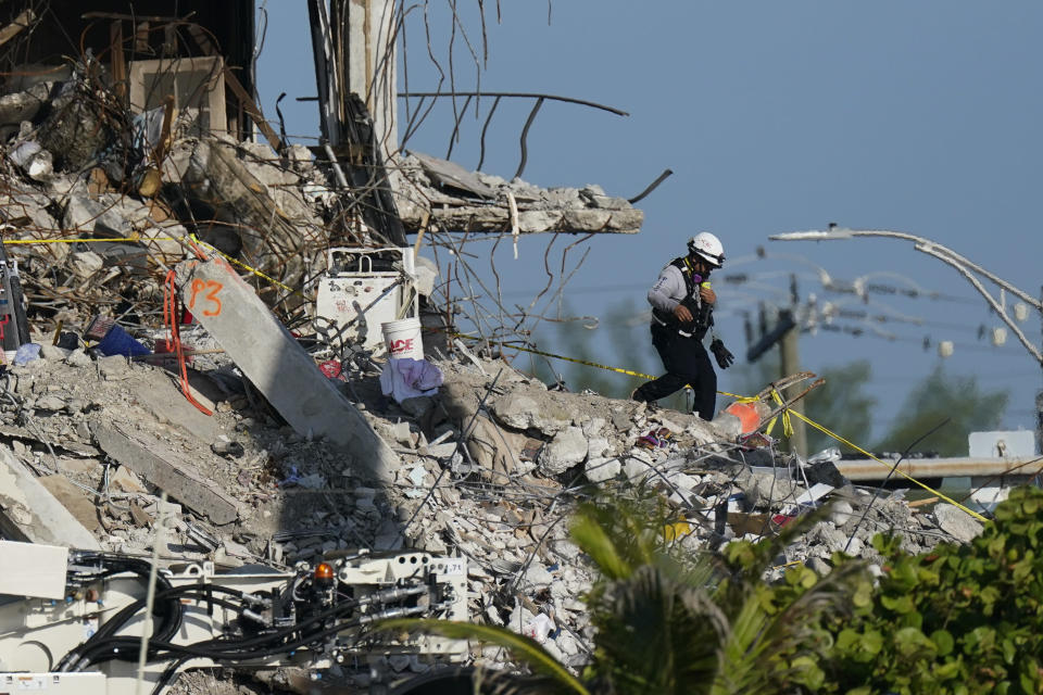A man descends from the rubble pile, as members of the search and rescue personnel work atop the rubble at the Champlain Towers South condo building, where scores of people remain missing one week after it partially collapsed, Friday, July 2, 2021, in Surfside, Fla. (AP Photo/Mark Humphrey)