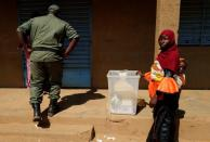 An electoral worker stands beside a ballot box at a polling station ahead of the presidential and legislative elections, in Ouagadougou