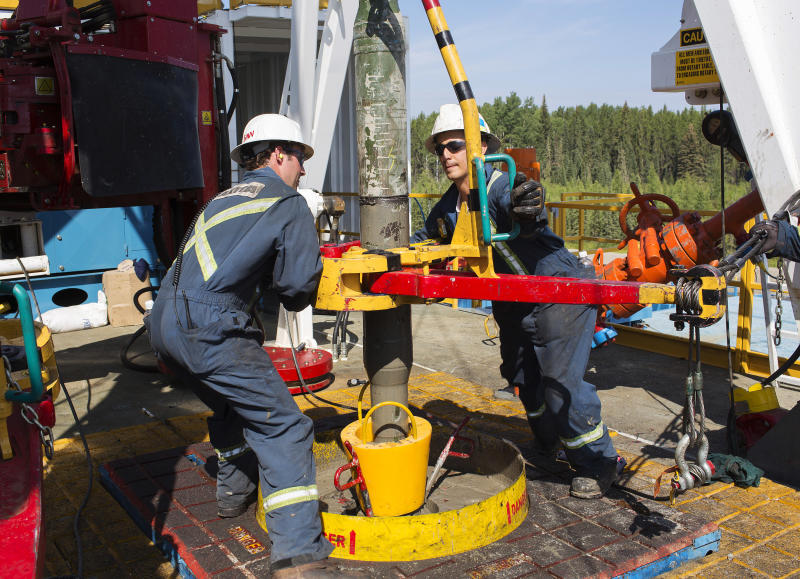 Oil rig floorhands from Akita Drilling work on an oil rig at the Cenovus Energy Christina Lake Steam-Assisted Gravity Drainage (SAGD) project 120 km (74 miles) south of Fort McMurray, Alberta, August 15, 2013. Cenovus currently produces 100,000 barrels of heavy oil per day at their Christina Lake tar sands project. REUTERS/Todd Korol (CANADA - Tags: ENERGY BUSINESS)
