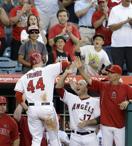 Los Angeles Angels' Mark Trumbo (44) is congratulated on his home run that tied the score against the Chicago Cubs in the eighth inning of a baseball game in Anaheim, Calif., Wednesday, June 5, 2013. (AP Photo/Reed Saxon)