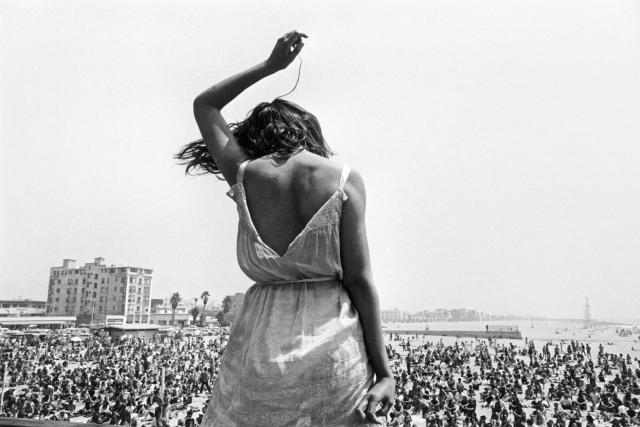 "<p>Venice Beach Rock Festival, Calif., 1968. ""Fifteen years since my first trip West, I have some new thoughts about gloryville. Every idea that Western man explores in his pursuit of the best of all possible worlds will be searched at the head lab — California. Technological and spiritual quests vibrate throughout the state, intermingling, often creating the ethereal. It is from this freewheeling potpourri of search that the momentary ensembles in space spring, presenting to the photographer his surrealistic image. However, to the Californians it is all so ordinary, almost mundane. The sensibility of these conditioned victims is where it is all at, right, left, up and down. Our future is being determined in the lab out West. There, a recent trip blew my mind across this state of being, as I collected images along the way to remember the transient quality of the Big Trip."" — Dennis Stock, September 1968 (preface to <em>California Trip</em>, Grossman Publishers, 1970). (© Dennis Stock/Magnum Photos) </p>"