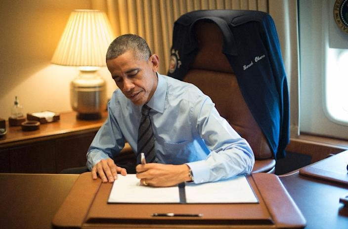 US President Barack Obama signs two Presidential Memoranda associated with his Executive Actions on immigration in his office on board Air Force One in Las Vegas, Nevada, November 21, 2014 (AFP Photo/Jim Watson)