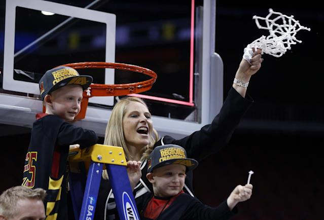 Maryland coach Brenda Frese holds up the net while joined by her sons, Tyler, left, and Markus, after Maryland defeated Louisville 76-73 in a regional final of the NCAA women's college basketball tournament Tuesday, April 1, 2014, in Louisville, Ky. (AP Photo/John Bazemore)
