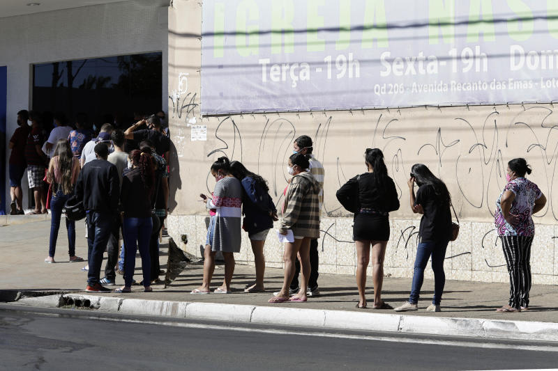 People wait outside the state-run bank Caixa Economica in Brasilia, Brazil, Thursday, July 23, 2020. People are trying to get access to $150 dollars of government aid for the unemployed and independent workers affected by the COVID-19 pandemic lockdown. (AP Photo/Eraldo Peres)