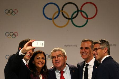 International Olympic Committee (IOC) member and Co-Chairman of Paris 2024 Tony Estanguet, Mayor of Paris Anne Hidalgo, IOC President Thomas Bach, Mayor of Los Angeles Eric Garcetti and Chairman of Los Angeles 2028 Casey Wasserman pose for a slefie after news conference during the 131st IOC session in Lima, Peru, September 13, 2017. REUTERS/Guadalupe Pardo