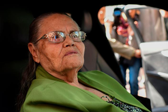 An elderly woman is seen seated in a car and looking out the window.