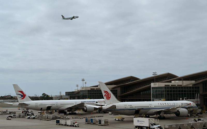 Air China and China Eastern planes wait at the gates at Los Angeles International Airport in September last year - DANIEL SLIM /AFP