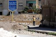 A boy stands near the entrance of the Waer district in the central Syrian city of Homs, Syria September 19, 2016. REUTERS/Omar Sanadiki
