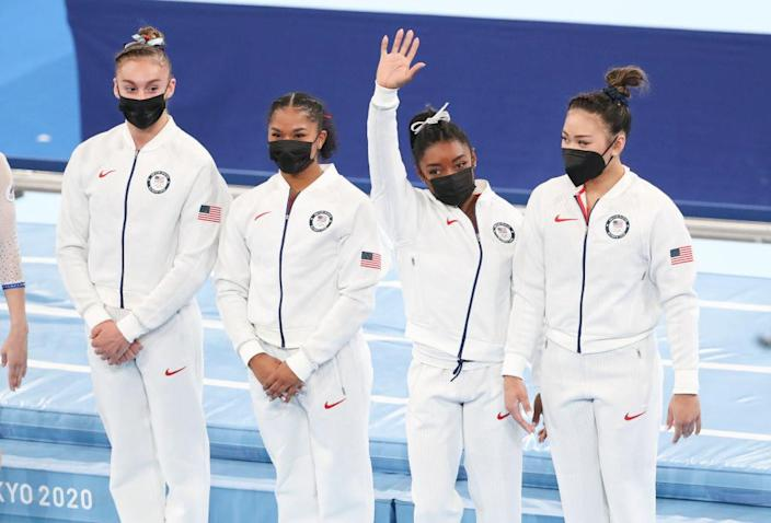Biles waving as she stands with her teammates on the floor of the arena