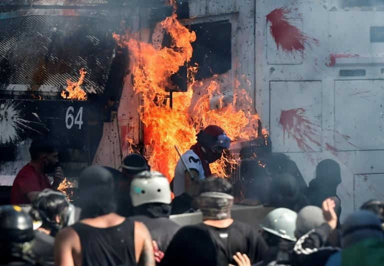Demonstrators set a police vehicle on fire during clashes between security forces and protesters marking the first anniversdary of Chile's social unrest over inequality