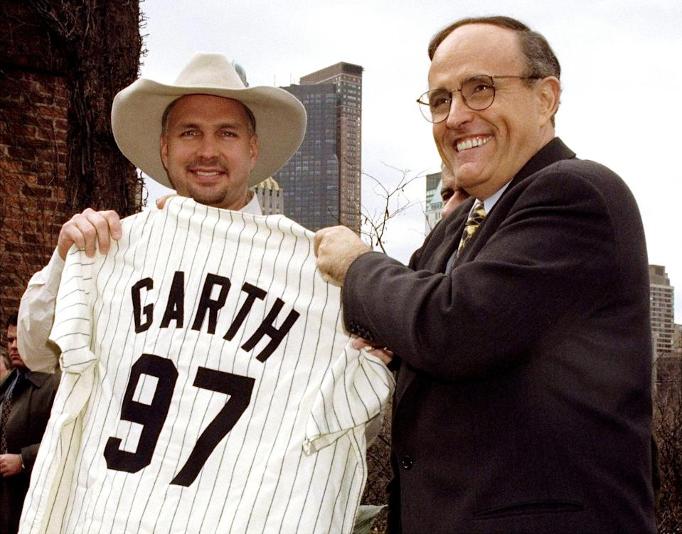 <p>Then-New York City Mayor Rudy Giuliani presents Brooks with a custom Yankees baseball uniform during a 1997 press conference on the roof of the Arsenal Building in Central Park. </p>