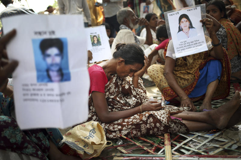 A woman grieves while others hold up pictures of their missing relatives at a school turned make-shift morgue where family members come to identify and claim bodies found in the garment factory building collapse, Thursday, May 2, 2013, in Savar, near Dhaka, Bangladesh. Rescuers found more bodies in the concrete debris of a collapsed garment factory building Thursday and authorities said it may take another five days to clear the rubble. In addition to the 430 confirmed dead, police report another 149 people are still missing in what has become the worst disaster for Bangladesh's $20 billion-a-year garment industry that supplies global retailers.(AP Photo/Wong Maye-E)