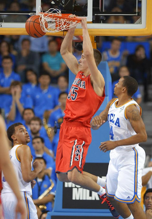 Arizona center Kaleb Tarczewski, center, dunks as UCLA forward Kyle Anderson, left, and guard Norman Powell watch during the second half of an NCAA college basketball game, Thursday, Jan. 9, 2014, in Los Angeles. (AP Photo/Mark J. Terrill)