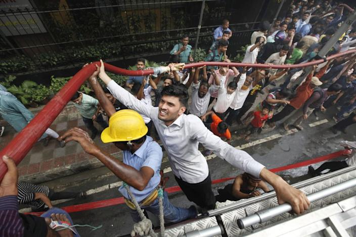 Locals help firefighters douse a fire in a multi-storied office building in Dhaka, Bangladesh, March 28, 2019. (AP Photo/Mahmud Hossain Opu)