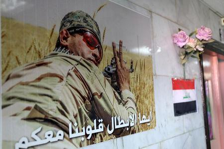 """A poster of a Hashid Shaabi fighter is seen in a hospital run by the Shia militia group in Hilla, Iraq, July 5, 2018. The text on the poster reads, """"Heroes, our hearts with you"""". Picture taken July 5, 2018. REUTERS/Marius Bosch"""