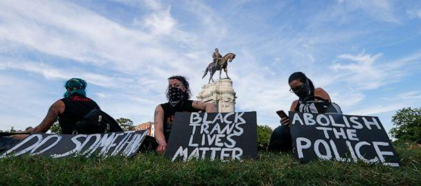 PHOTO: Protesters hold signs around the statue of Confederate Gen. Robert E. Lee on Monument Avenue, June 2, 2020, in Richmond, Va. The crowd protesting police brutality chanted 'Tear it down.' (Steve Helber/AP)