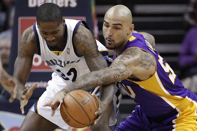 Los Angeles Lakers' Robert Sacre, right, gets a steal from Memphis Grizzlies' Ed Davis (32) during the first half of an NBA basketball game in Memphis, Tenn., Tuesday, Dec. 17, 2013. (AP Photo/Danny Johnston)