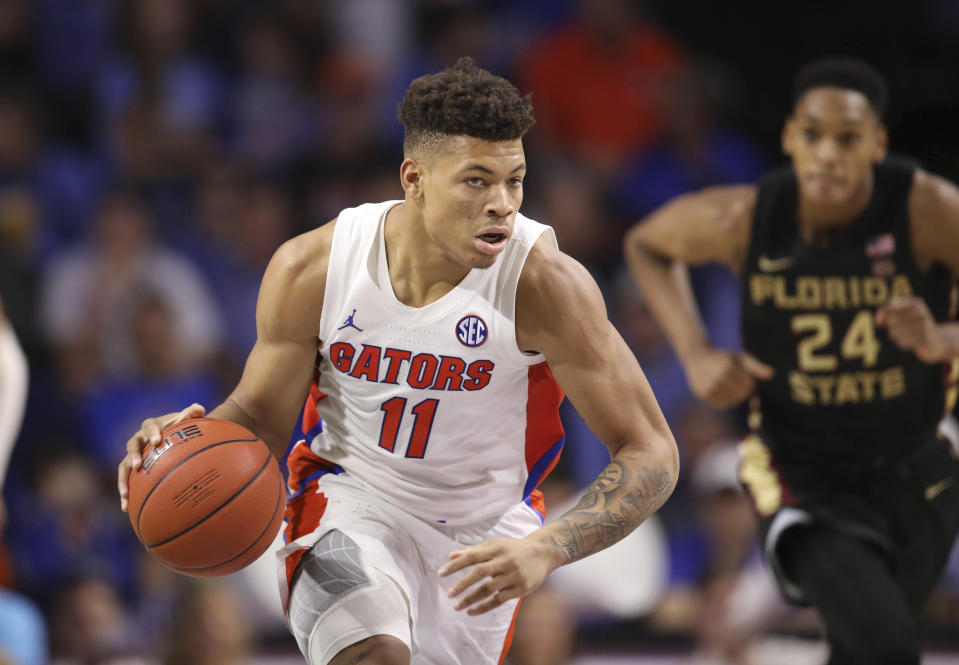 Florida forward Keyontae Johnson (11) dribbles up court past Florida State guard Devin Vassell (24) during the second half of an NCAA college basketball game Sunday, Nov. 10, 2019, in Gainesville, Fla. (AP Photo/Matt Stamey)