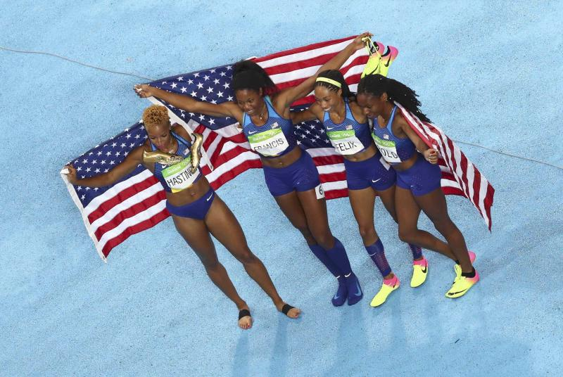 Courtney Okolo, Natasha Hastings, Phyllis Francis and Allyson Felix pose with their national flags after winning the gold. (REUTERS)