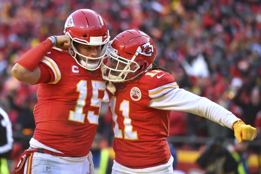 Kansas City Chiefs' Patrick Mahomes (15) celebrates with Demarcus Robinson after running for a touchdown during the first half of the NFL AFC Championship football game Sunday, Jan. 19, 2020, in Kansas City, MO. (AP Photo/Ed Zurga)