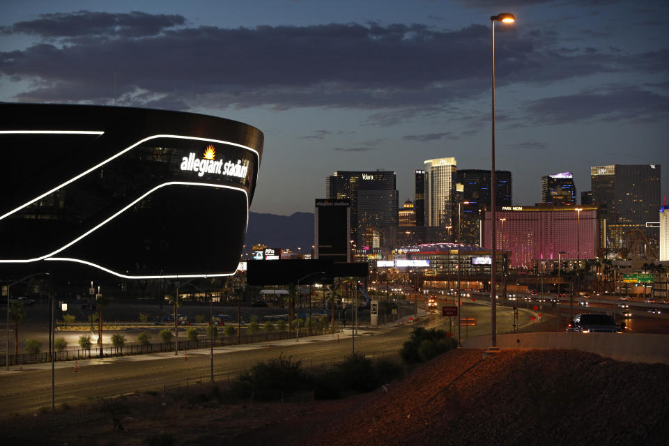 An exterior view of the new Allegiant Stadium with the Las Vegas Strip in the background.