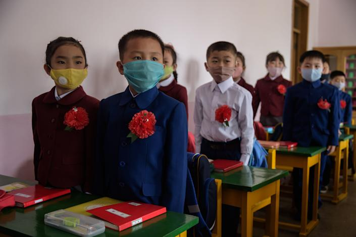 Primary school children wearing face masks as a protective measure against the COVID-19 novel coronavirus attend a class at Hasin Primary School in Sosong District in Pyongyang following the re-opening of schools on June 3, 2020.
