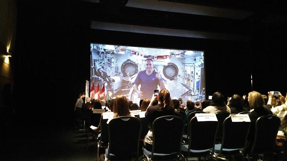 Canadian astronaut David Saint-Jacques (on screen) calls down from the International Space Station to a group of schoolchildren at the Canada Aviation and Space Museum in Ottawa on Feb. 7, 2019. <cite>Elizabeth Howell</cite>