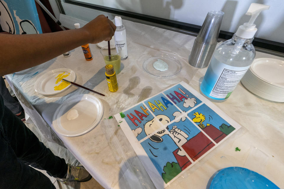 "Jesse McCarty, 14, cleans his brush next to diagram of a ""Peanuts"" mural he is helping to paint that will be placed in the outpatient pediatric floor of One Brooklyn Health at Brookdale Hospital, Thursday, Oct. 1, 2020, in the Brooklyn borough of New York. The virus pandemic won't stop Charlie Brown, Snoopy or the ""Peanuts"" gang from marking an important birthday and they're hoping to raise the spirits of sick kids while they celebrate. The beloved comic marks its 70th anniversary this week with new lesson plans, a new TV show and a philanthropic push that includes donating ""Peanuts"" murals for kids to paint in 70 children's hospitals around the globe, from Brooklyn to Brazil. (AP Photo/Mary Altaffer)"