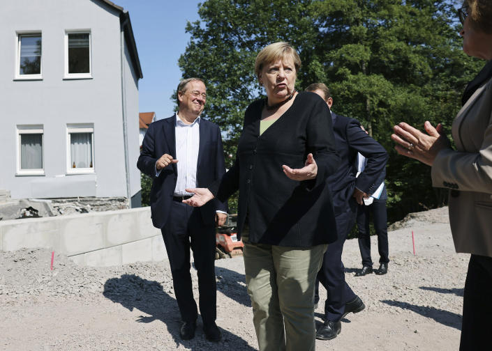 German Chancellor Angela Merkel, centre, with Armin Laschet, left, candidate for chancellor of the CDU/CSU and chairman of the CDU, talk to Petra Beckefeld, right, from the road construction company Strassen, as they vistit areas affected by flooding, in Hagen, Germany, Sunday, Sept. 5, 2021. (Oliver Berg/Pool Photo via AP