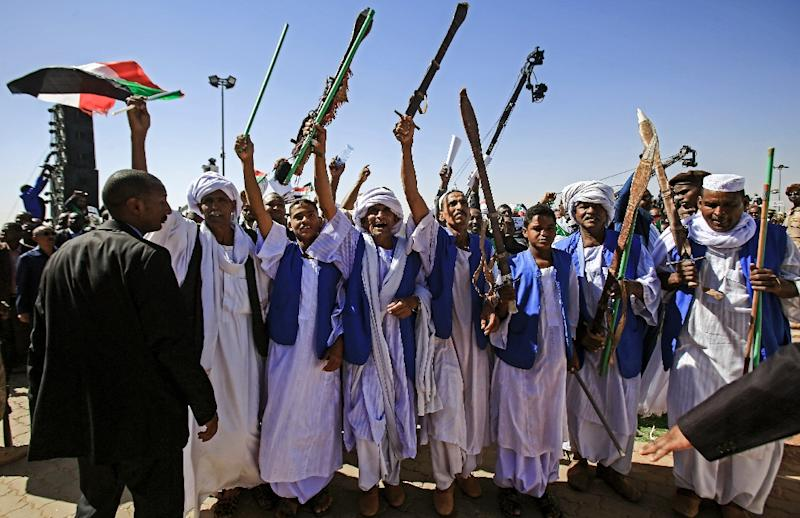 Raising sticks and swords, a group attends a rally in support of Sudanese President Omar al-Bashir in Khartoum on January 9, 2019 (AFP Photo/ASHRAF SHAZLY)
