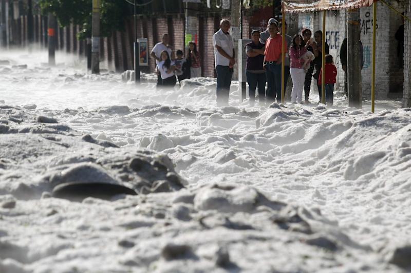 People remain on the sidewalk of a street covered with hail in the eastern area of Guadalajara, Jalisco state, Mexico, on June 30, 2019.