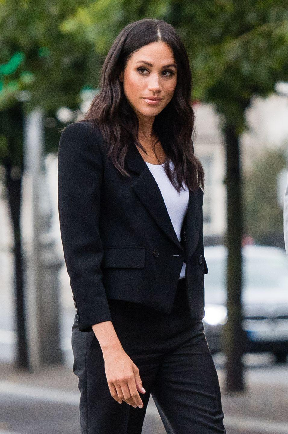 """<p><a href=""""https://www.byrdie.co.uk/meghan-markle-low-bun--5b55b3147419a/slide3"""" rel=""""nofollow noopener"""" target=""""_blank"""" data-ylk=""""slk:According to Byrdie UK"""" class=""""link rapid-noclick-resp"""">According to Byrdie UK</a>, """"a low bun is like a form of damage control. Markle can wear one all day and then quickly unwind it—letting her loose waves fall beyond her shoulders, ready for the evening's function."""" </p>"""