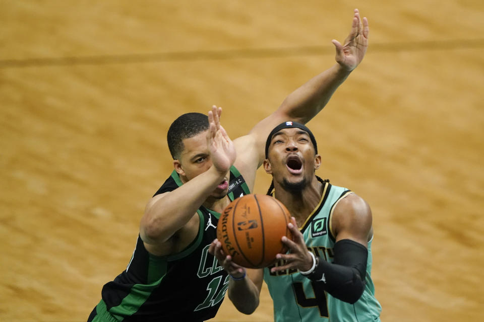 Charlotte Hornets guard Devonte' Graham drives to the basket past Boston Celtics forward Grant Williams during the first half of an NBA basketball game on Sunday, April 25, 2021, in Charlotte, N.C. (AP Photo/Chris Carlson)