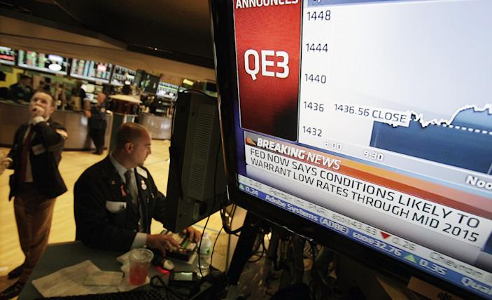 Specialist Frank Babino, center, works at his post on the floor of the New York Stock Exchange Thursday, Sept. 13, 2012. The Federal Reserve unleashed a series of aggressive actions Thursday intended to stimulate the still-weak economy by making it cheaper for consumers and businesses to borrow and spend. (AP Photo/Richard Drew)