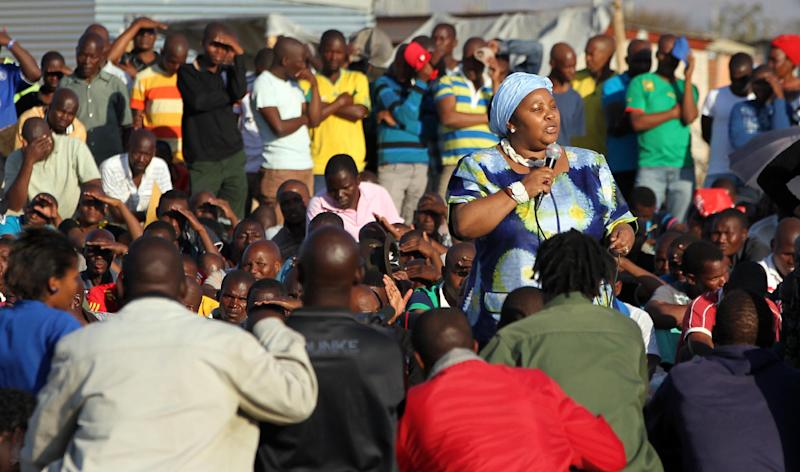 South Africa's Minister of Defence Nosiviwe Mapisa-Nqakula addresses mine workers at the Lonmin mine near Rustenburg, South Africa, Tuesday, Aug. 21, 2012. Miners Workers trickled in Tuesday at the Lonmin platinum mine where 44 people have died in a wildcat strike, as South Africa urged the company to suspend an ultimatum to return to work. (AP Photo/Themba Hadebe)