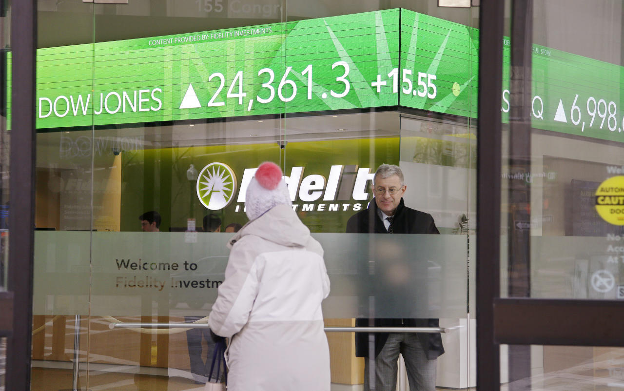 "FILE- In this Feb. 6, 2018, file photo, a woman walks through the front doors at the Fidelity Investments office on Congress Street as the ticker displays stock market numbers in Boston. At Fidelity's retail brokerage customers continued to put in more buy orders than sells after the S&P 500 began falling from its peak set on Jan. 26, 2018. ""Millennials and Gen Xers are definitely taking advantage of these prices and taking advantage of the sell-off,"" said Scott Ignall, senior vice president and head of online brokerage technology at Fidelity. (AP Photo/Stephan Savoia, File)"