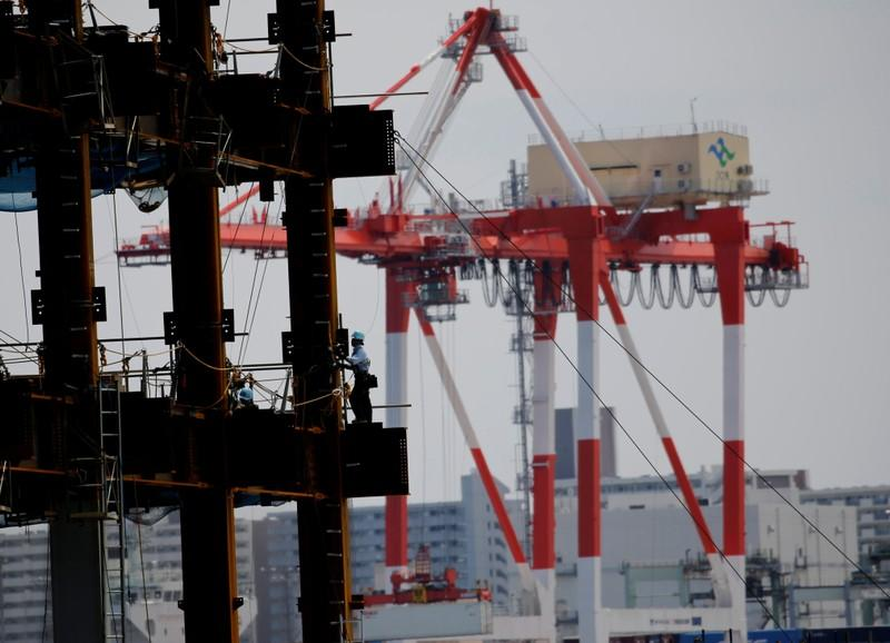 FILE PHOTO: A man works in a construction site at an industrial port in Tokyo