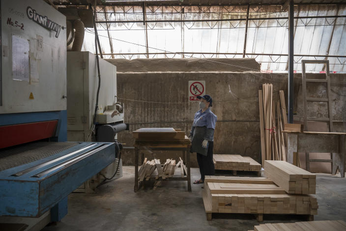 A worker prepares wood to assemble saunas at Hongyuan Furniture in Guangzhou, China, Aug. 4, 2020. (Andrea Verdelli/The New York Times)