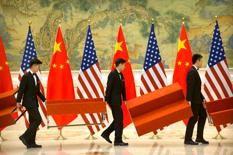 Aides set up platforms before a group photo with members of U.S. and Chinese trade negotiation delegations at the Diaoyutai State Guesthouse in Beijing, Friday, Feb. 15, 2019. (AP Photo/Mark Schiefelbein, Pool)