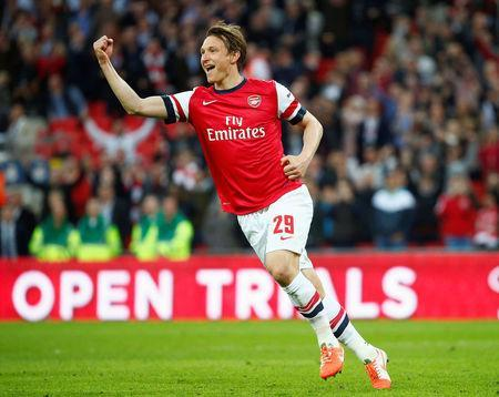 FILE PHOTO: Arsenal's Kim Kallstrom celebrates after scoring a penalty in their penalty shoot-out during their English FA Cup semi-final soccer match against Wigan Athletic at Wembley Stadium in London April 12, 2014. REUTERS/Eddie Keogh/File Photo