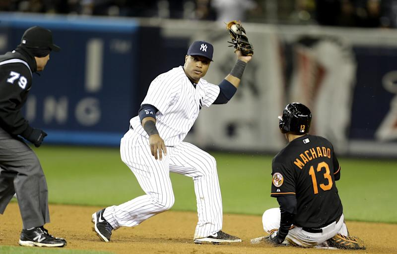 New York Yankees second baseman Robinson Cano, center, waits for the call from second base umpire Manny Gonzalez, left, after tagging Baltimore Orioles' Manny Machado, right, for the third out of a triple play during the eight inning of a baseball game at Yankee Stadium in New York, Friday, April 12, 2013. (AP Photo/Julio Cortez)